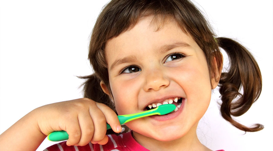 Little girl smiling and brushing her teeth